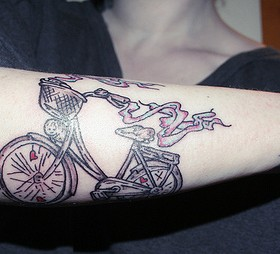 Colorful black bicycle tattoo on arm
