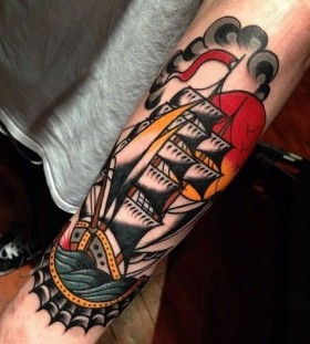 Colorful black ship tattoo on arm