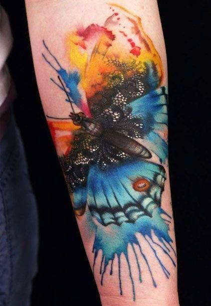 Colorful butterfly and lace tattoo on arm