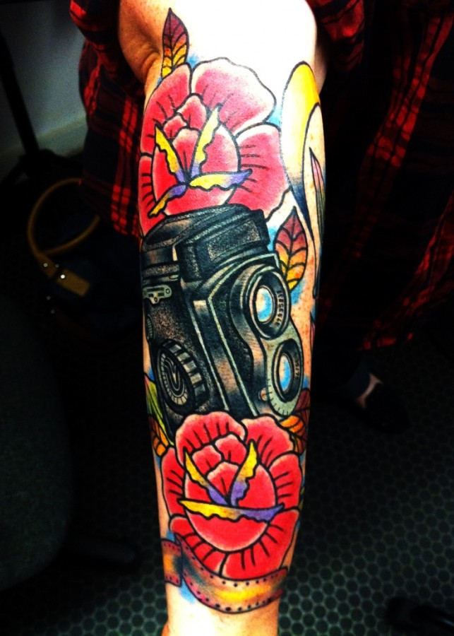 Colorful flowers and camera tattoo on arm