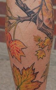 Colorful leafs and tree tattoo on leg