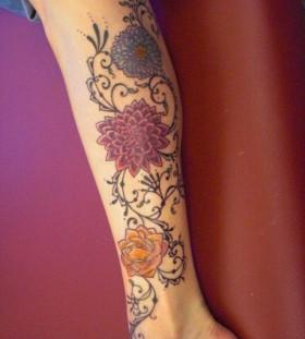 Colorful lovely flower tattoo on leg