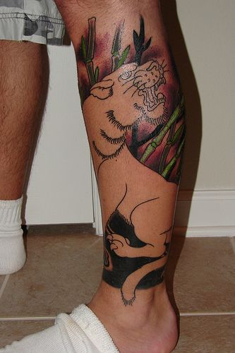Colorful nature and tiger tattoo on leg