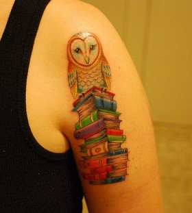 Colorful owl and book tattoo on arm