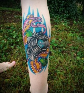 Colorful purple camera tattoo on leg