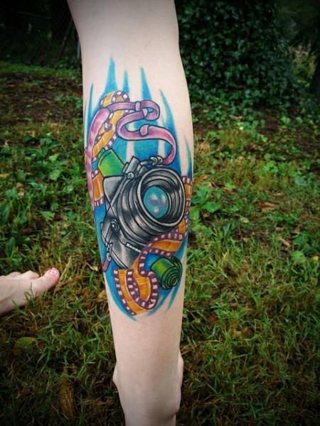 Colorful purple camera tattoo on leg