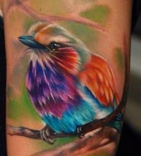 Colorful simple bird tattoo on arm