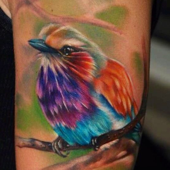 Colorful simple bird tattoo on arm