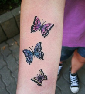 Colorful small butterfly tattoo on arm