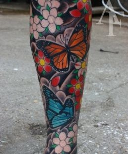 Colorful women butterfly tattoo on leg