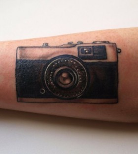 Cute black camera tattoo on arm