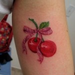 Cute red cherry tattoo on arm