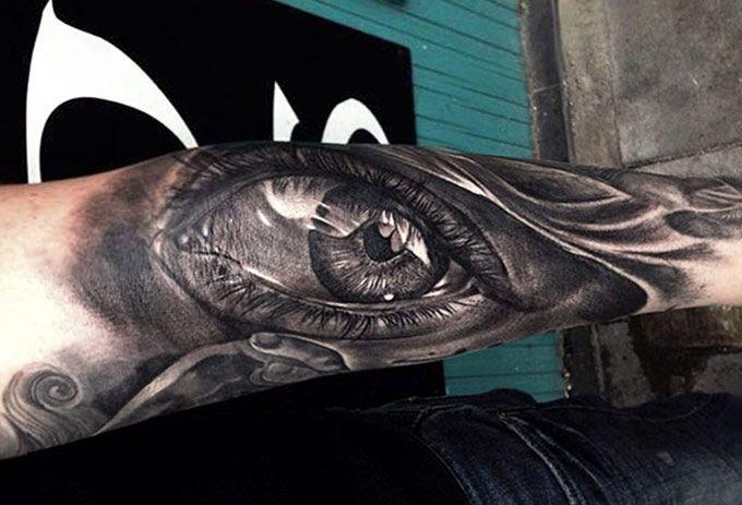 Deep black eye tattoo on arm