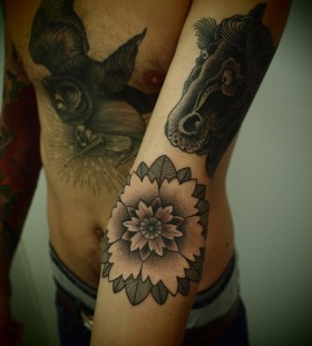 FLower and black horse tattoo on arm