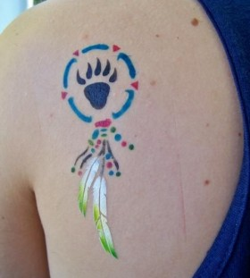 Feather and colorful black bear tattoo on shoulder