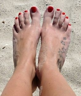 Foot and sand star tattoo on leg