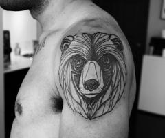 Gorgeous black ornaments of bear tattoo on shoulder