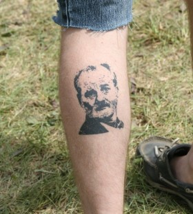 Great men's face tattoo on leg