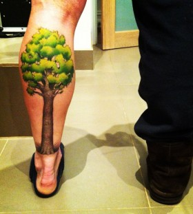 Green and brown tree tattoo on leg