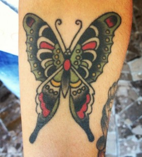 Green and red butterfly tattoo on leg