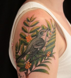 Green leaf and bird tattoo