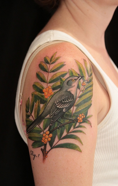 Green leaf and bird tattoo