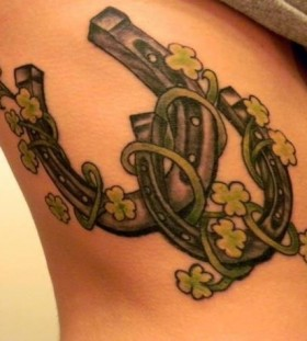 Green leafs and horse shoe tattoo