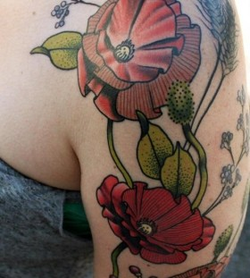 Green leafs and poppies tattoos on arm