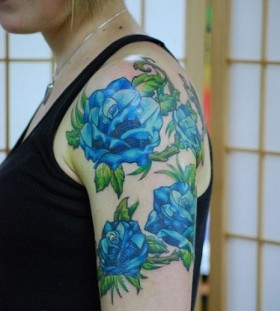 Green leafs and rose blue flowers tattoos