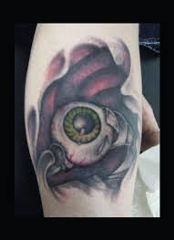 Green owal eye tattoo on leg