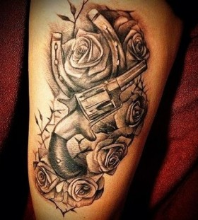 Gun, roses and horse shoe tattoo