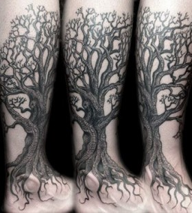 Huge black tree tattoo on leg