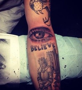 King, believe, tiger and eye tattoo on arm