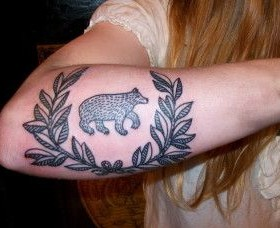 Leafs and black bear tattoo on arm