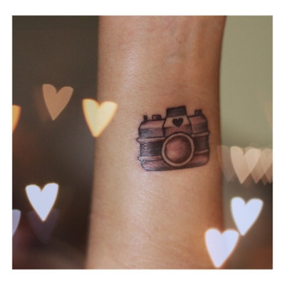 Lovely heart and camera tattoo on arm