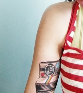 Lovely red heart and rainbow color with camera tattoo on arm