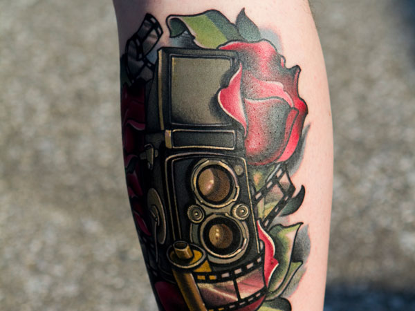 Magical red rose and camera tattoo on leg