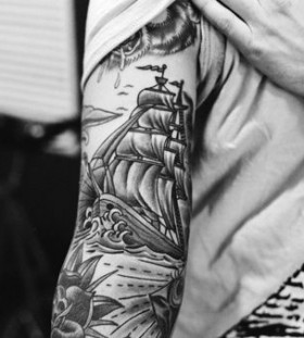 Men's black ship tattoo on arm