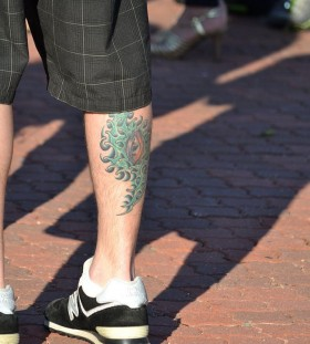 Men's green eye tattoo on leg