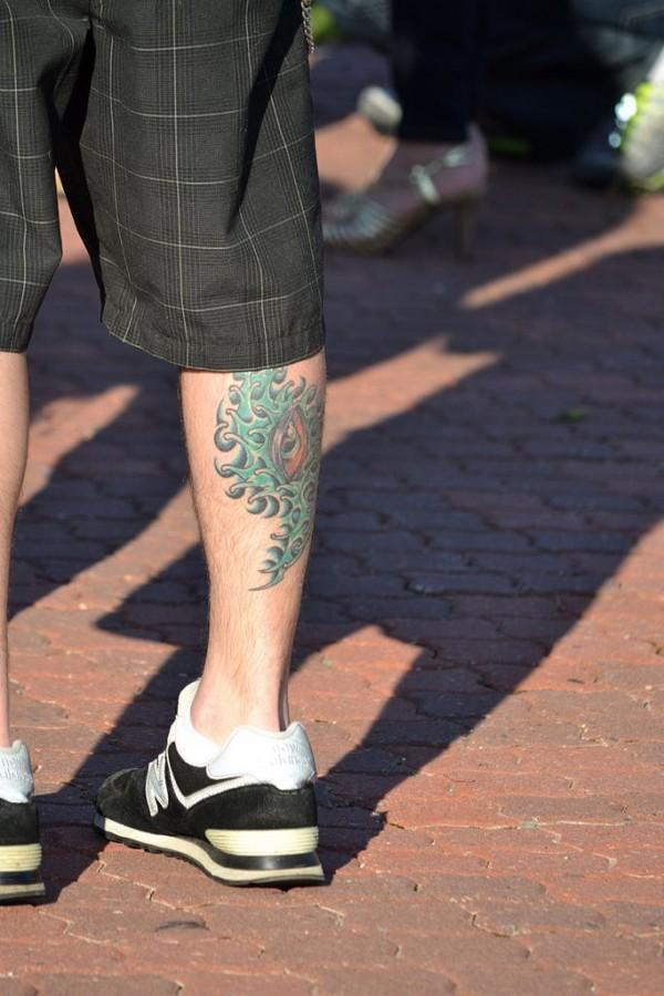 Men's green eye tattoo on leg