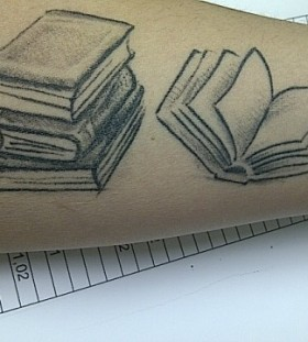 Numbers and black book tattoo on arm