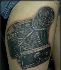 Old pretty camera tattoo on leg