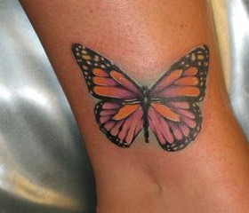 Pink small butterfly tattoo on leg