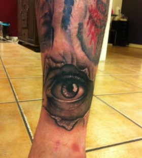 Pretty black and red eye tattoo on leg