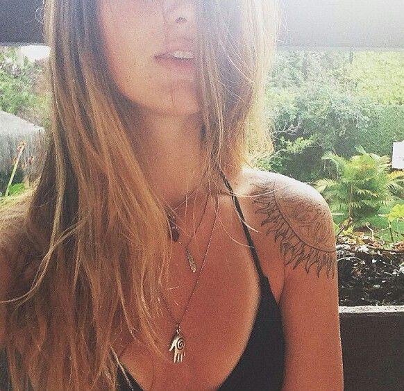 Pretty blonde girl sun tattoo on shoulder
