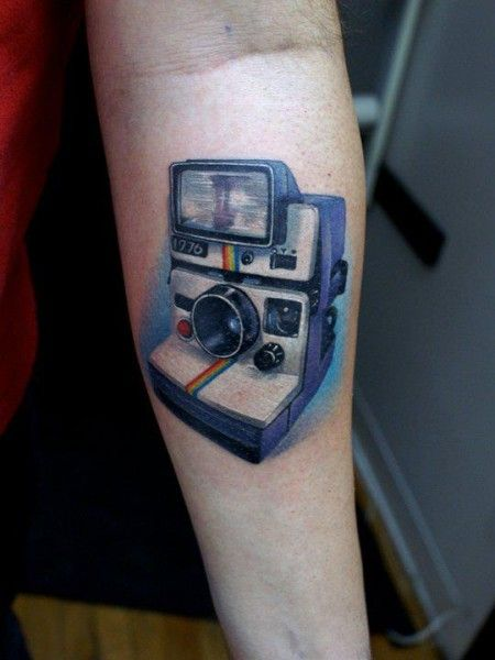 Pretty blue camera tattoo on arm