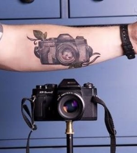 Realistic black camera tattoo on arm