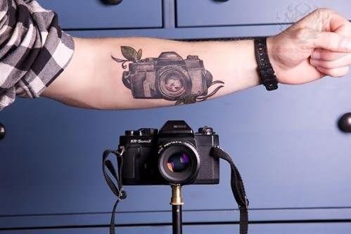 Realistic black camera tattoo on arm