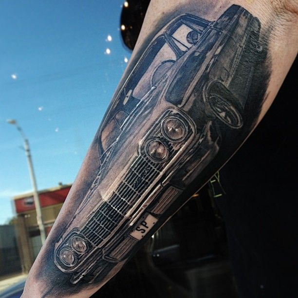 Realistic black car tattoo on arm