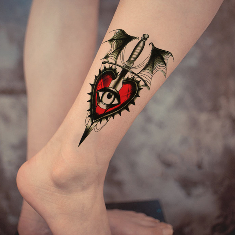 Red and black heart with eye tattoo on leg
